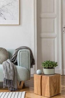 フレーム、緑のソファ、木製家具、植物、アクセサリーを備えたスタイリッシュなリビングルームのインテリアデザインの居心地の良い創造的な構成。白い壁、寄木細工の床。