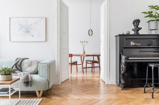 緑のソファ木製家具ピアノとアクセサリーを備えたスタイリッシュなリビングルームのインテリアデザインの居心地の良い創造的な構成。