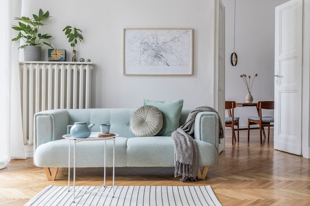 Уютная и креативная композиция стильного дизайна интерьера гостиной с зеленым диваном, деревянной мебелью, растениями и аксессуарами. белые стены, паркетный пол.