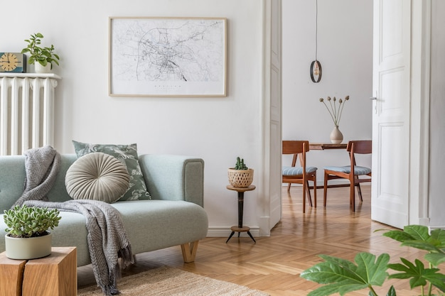 緑のソファ、木製家具、植物、アクセサリーを備えたスタイリッシュなリビングルームのインテリアデザインの居心地の良い創造的な構成。白い壁、寄木細工の床。