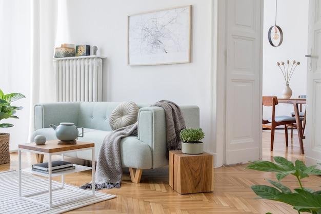 モックアップポスターフレーム、緑のソファ、木製家具、植物、アクセサリーを備えたスタイリッシュなリビングルームのインテリアデザインの居心地の良い創造的な構成。白い壁、寄木細工の床。テンプレート。