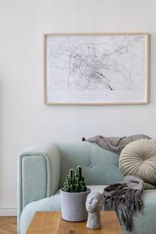 Уютная и креативная композиция стильного дизайна интерьера гостиной с распечатанной картой, зеленым диваном, деревянной мебелью, растениями и аксессуарами. белые стены, паркетный пол.