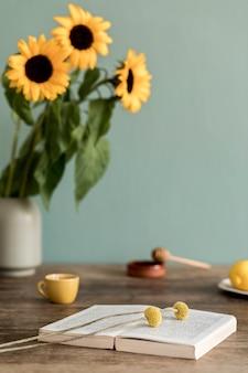 Уютная и стильная композиция креативной столовой с деревянной консолью, подсолнухами и личными аксессуарами. зеленая стена, детали. красивое и солнечное утро.