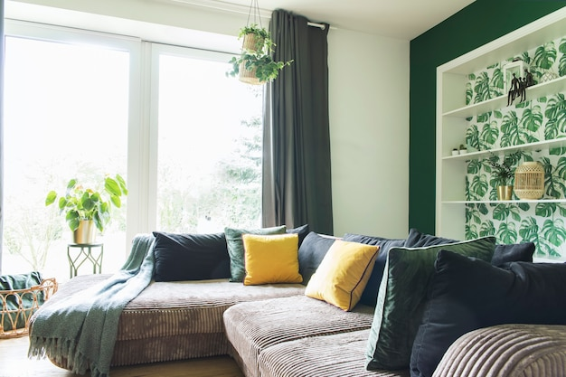큰 코너 소파, 가구, 베개 및 기타 액세서리와 장식으로 아늑하고 세련된 거실 인테리어 디자인. 녹색 벽, 지중해 스타일.