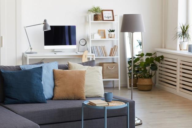 Cozy apartment interior in minimal scandinavian design and focus on grey sofa with decor elements