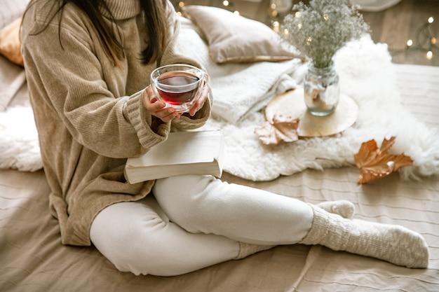 집에서 아늑한 가을, 책과 차를 쉬고있는 여자. 아늑한 삶의 방식. 구성의 신체 부위.
