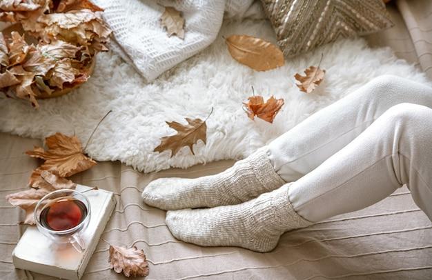 家で居心地の良い秋、本とお茶を休んでいる女性。居心地の良い生き方。構成の体の部分。
