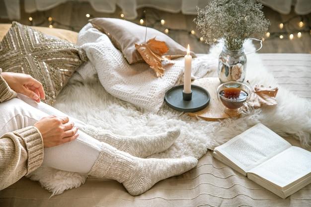 집에서 아늑한 가을, 책을 쉬고있는 여자. 아늑한 삶의 방식. 구성의 신체 부위.