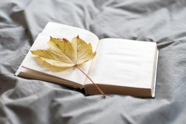 家で居心地の良い秋。黄色いカエデの葉の開いた本がベッドに横たわっています。