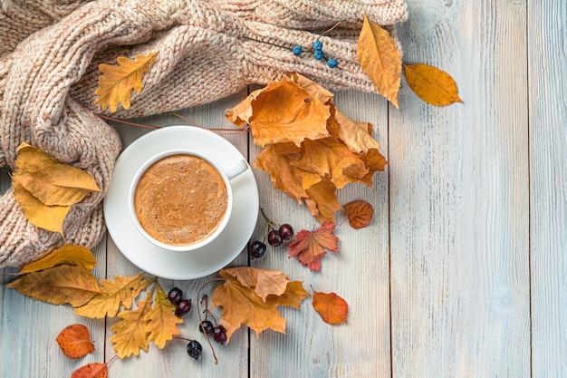 Уютный осенний фон с чашкой кофе, теплый свитер и листва