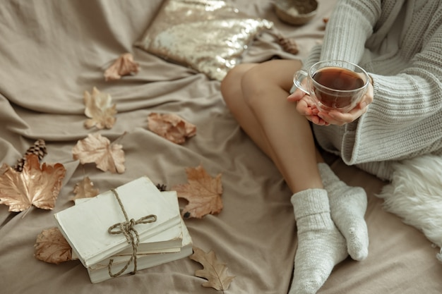 Cozy autumn background with female legs in warm socks, a cup of tea and autumn leaves in bed.