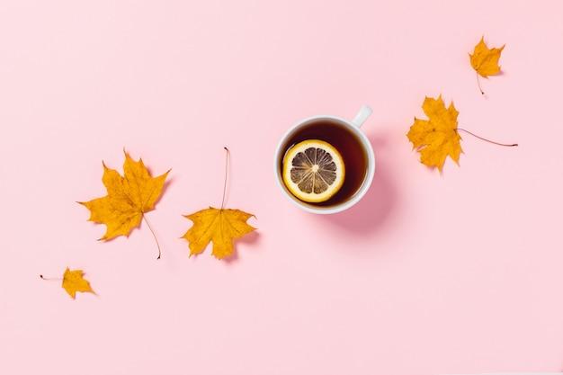 居心地の良い秋の組成物。レモンとカエデの葉のティーカップ。