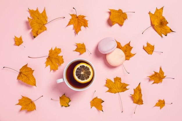 居心地の良い秋の組成物。レモンとカエデの葉のスライスとティーカップ。