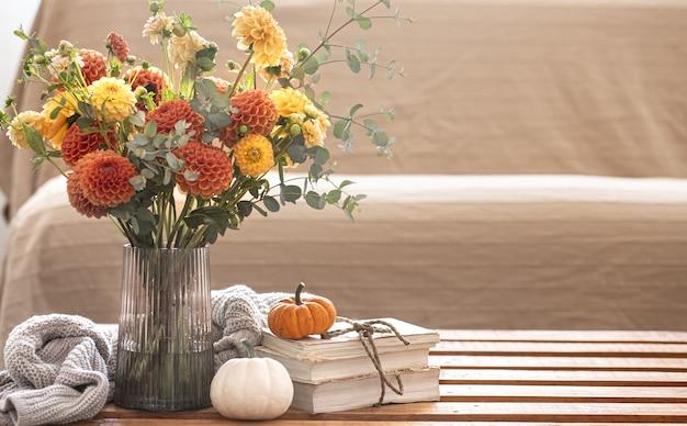Уютная осенняя композиция с букетом хризантем в вазе, тыквами и вязанным элементом на размытом фоне интерьера.
