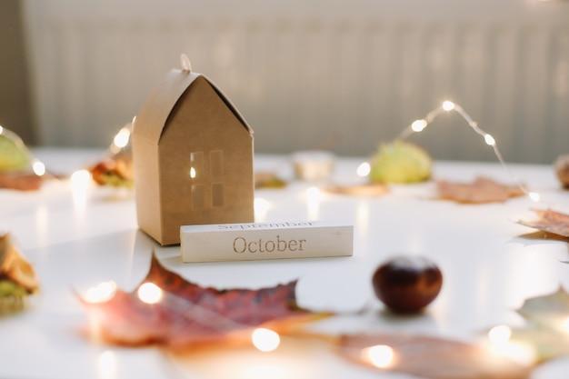Уютная осенняя композиция с бумажным домиком в окружении осенних листьев на белом столе