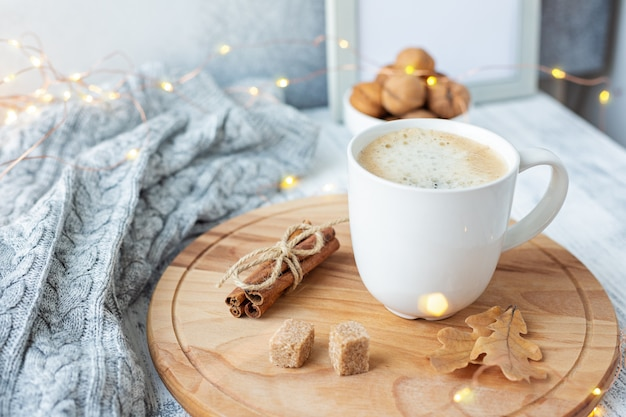 Cozy autumn composition with coffee mug, sweater, cinnamon, decorated with led lights