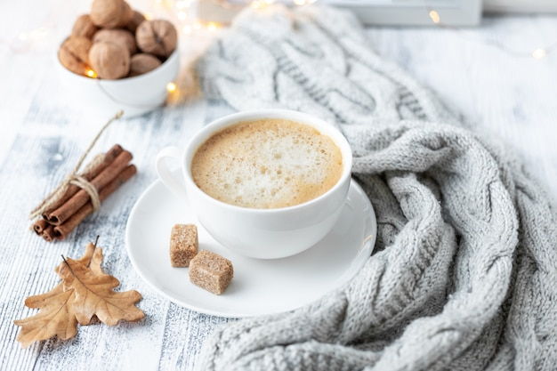 Cozy autumn composition with cup of coffee, brown sugar, knitted scarf, garland