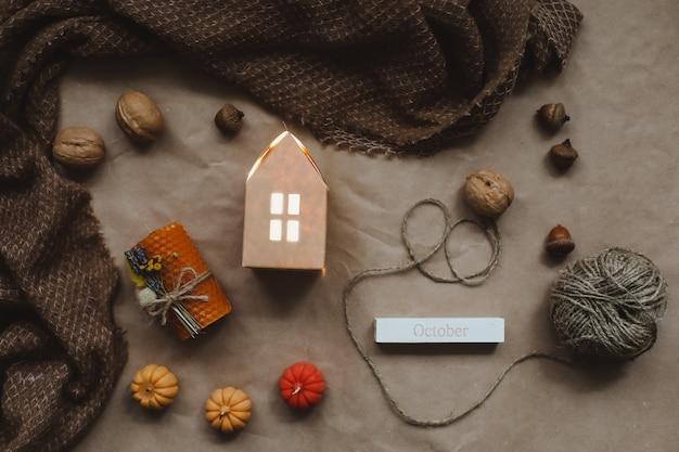 Уютная осенняя композиция с бумажным домиком в окружении свечей из осенних листьев и тыквенным видом сверху ...