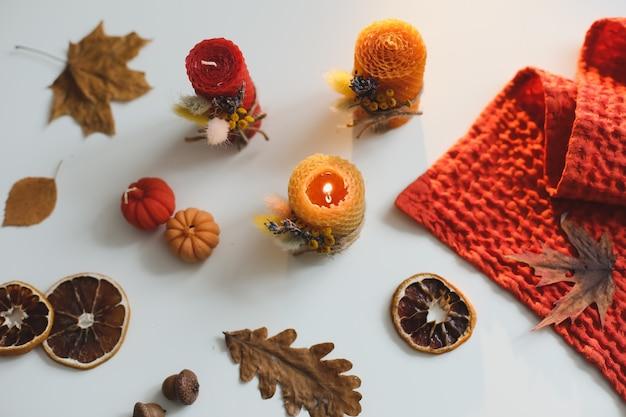 カボチャのワックスキャンドルと葉で居心地の良い秋の構成