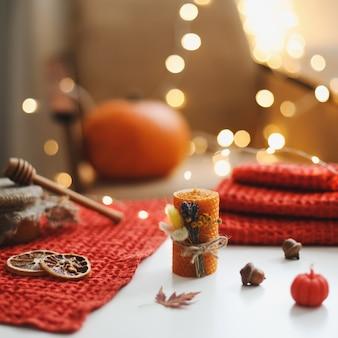 Уютная осенняя композиция с листьями тыквенных свечей и текстилем