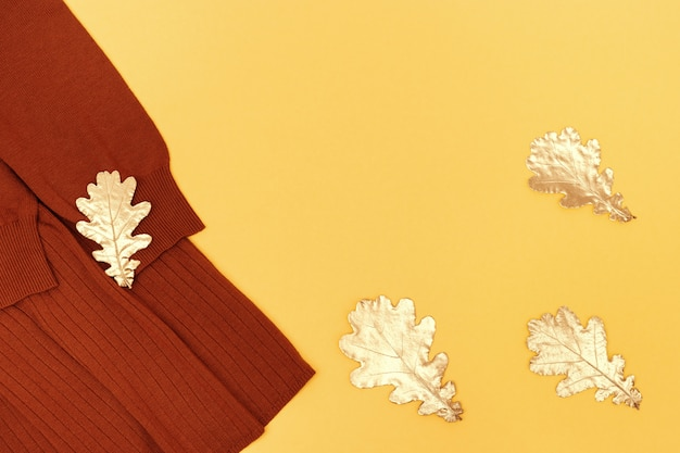 Cozy autumn female clothing decorated with golden oak leaves