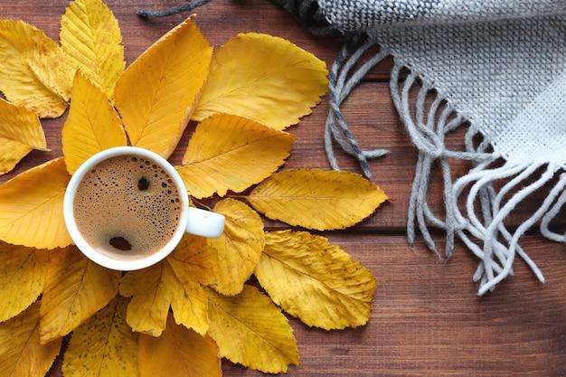 Уютная осенняя квартира с чашкой кофе в теплый плед и желтые осенние листья вид сверху
