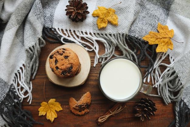 ミルクチョコレートチップクッキーのカエデの葉と暖かい毛布で居心地の良い秋のフラットレイ