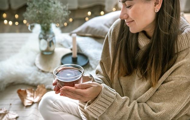 아늑한 가을 가정의 분위기, 손에 차 한 잔을 든 여인. 휴식과 편안함의 개념.
