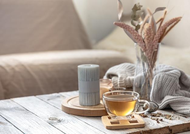 객실 내부의 흐릿한 배경에 차, 양초, 니트 요소가 있는 아늑한 가을 집 구성.