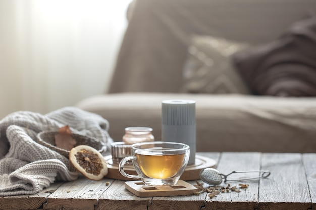Accogliente composizione domestica autunnale con una tazza di tè, candele e un elemento a maglia su uno sfondo sfocato dell'interno della stanza.
