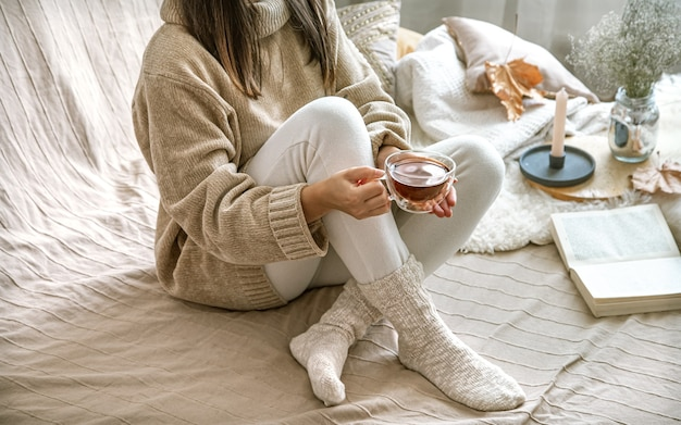 Cozy autumn at home, a woman in a knitted sweater with a cup of tea.