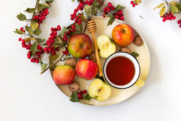 Cozy autumn hot spiced tea with honey, apples and red hawthorn berries on a tray. still life on white background. flat lay.