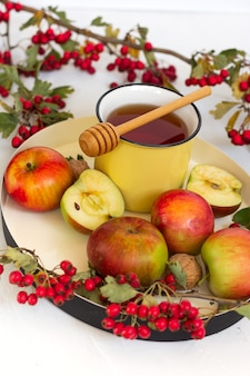 Cozy autumn hot spiced tea with honey, apples and red hawthorn berries on a tray. still life on white background.