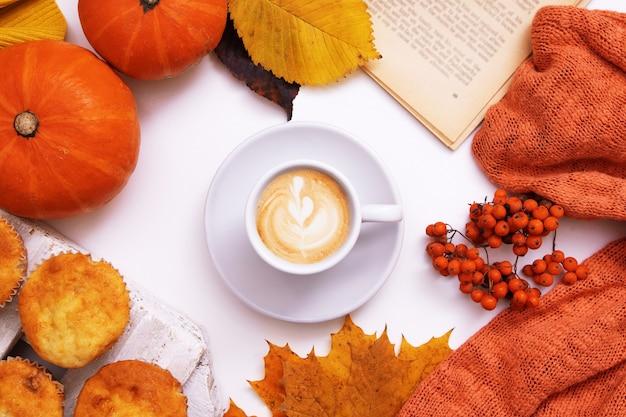 コーヒーとカボチャの葉のカボチャのセーターと本と居心地の良い秋のレイアウト