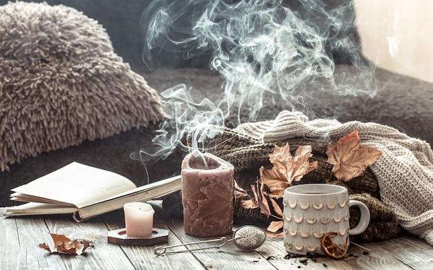 Уютный завтрак утра осени в сцене натюрморта кровати. дымящаяся чашка горячего кофе, чай стоит у окна. осень.