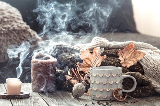 ベッドのある静物シーンで居心地の良い秋の朝の朝食。ホットコーヒーのカップを蒸し、窓の近くに立っているお茶。