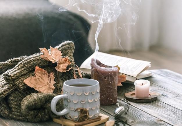 Уютный завтрак утра осени в сцене натюрморта кровати. дымящаяся чашка горячего кофе, чай стоит у окна.