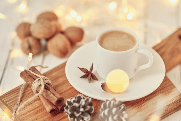 아늑한 가을 또는 겨울 개념입니다. 화환 조명 및 장식 커피 한잔 /