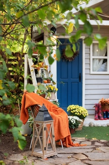 Cozy autumn patio with chair, plaid, plants, wooden lantern, potted chrysanthemums.