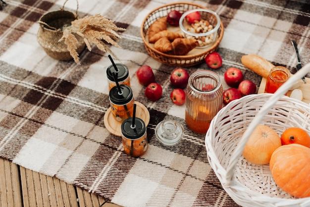 Cozy autumn picnic close-up pumpkin red apples jam on a plaid blanket