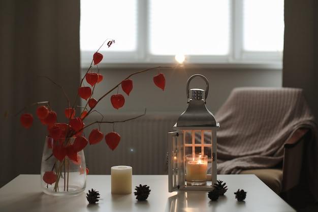 居心地の良い秋の静物キャンドル花瓶にオレンジ色のサイサリスの花の小枝と家のインテリアの詳細