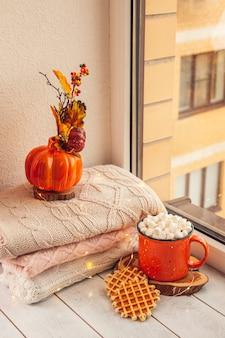 Уютный осенний натюрморт на подоконнике: теплые шерстяные кофточки, тыквы, кленовые листья и чашка какао с зефиром и вафлями.