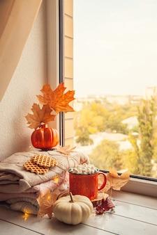 Уютный осенний натюрморт на подоконнике: теплые шерстяные кофточки, тыквы, кленовые листья и чашка какао с зефиром.