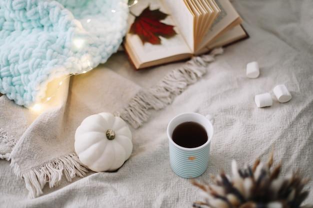 Уютный осенний натюрморт с чашкой сушеных листьев и белой тыквой Premium Фотографии