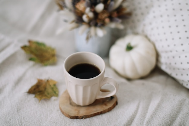 カップの乾燥した葉と白いカボチャのある居心地の良い秋の静物