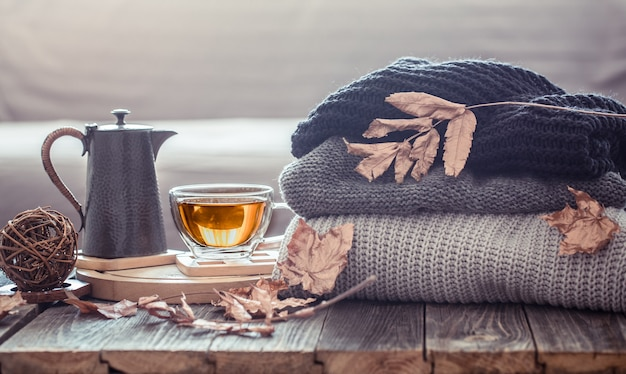 Accogliente natura morta autunnale con una tazza di tè e oggetti di arredo nel soggiorno. concetto di comfort domestico