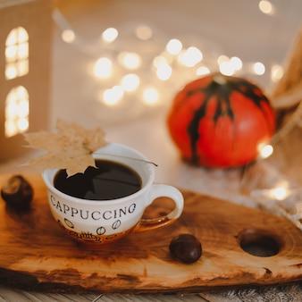 Уютный осенний натюрморт с тыквой и чашкой кофе на вязаном бежевом пледе с огнями боке Premium Фотографии