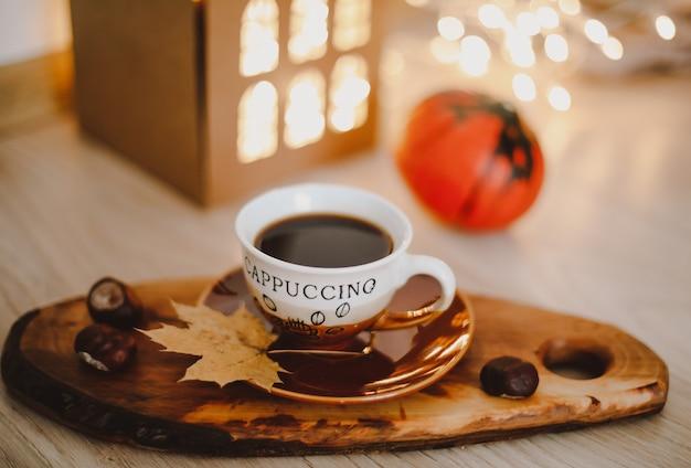 Уютный осенний натюрморт с тыквой и чашкой кофе с огнями боке