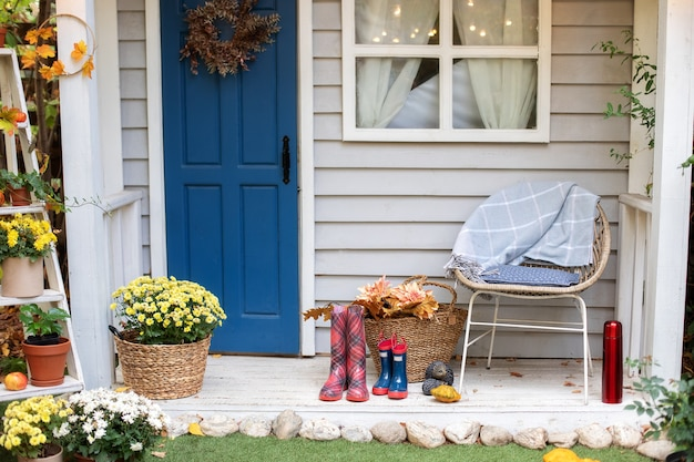 Cozy autumn terrace with chair, plaid, rubber boots, baskets with chrysanthemums and pumpkins.