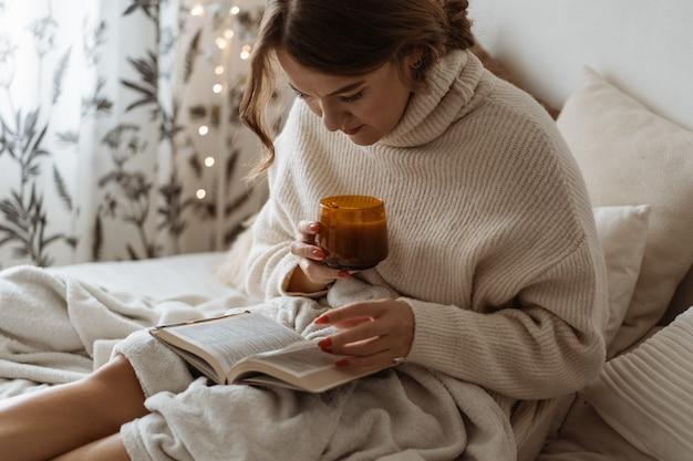 Уютный осенний зимний день. женщина пьет горячий чай и читает книгу. комфортный образ жизни